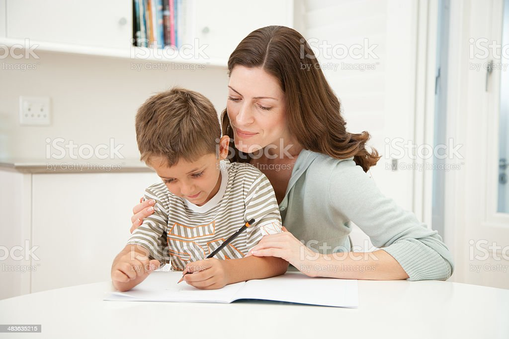 A mother helping her son with his homework stock photo