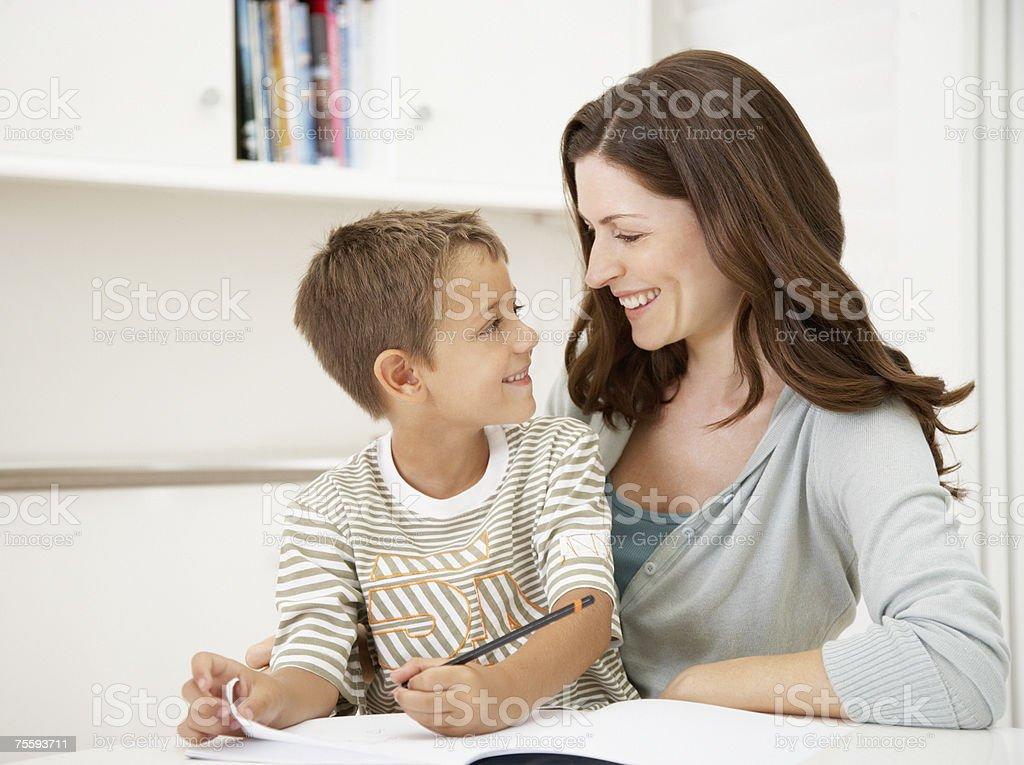 Uma mãe ajudando o seu filho com o seu trabalho de casa foto de stock royalty-free