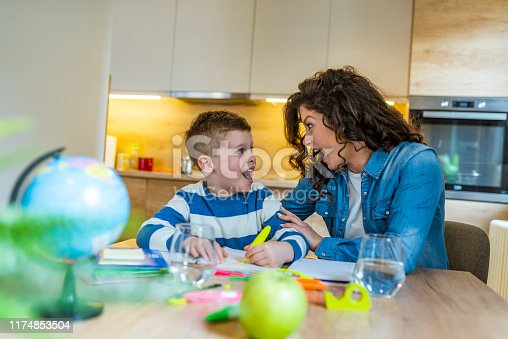 1020504438istockphoto Mother helping her son with homework in the kitchen 1174853504