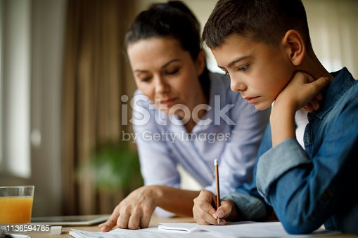 istock Mother helping her son with homework 1136594785