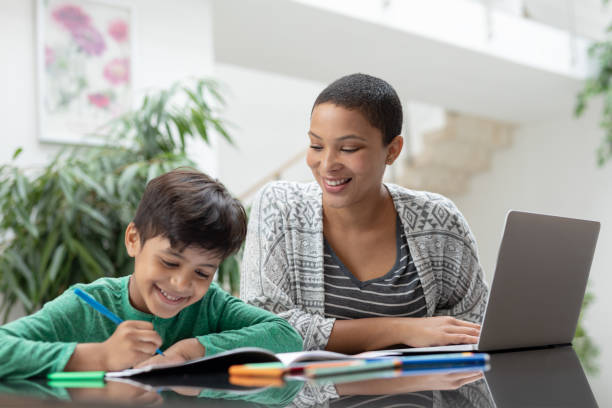 Mother helping his son with his homework on a table stock photo