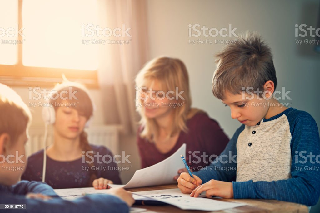 Mother helping kids doing their homeworks stock photo