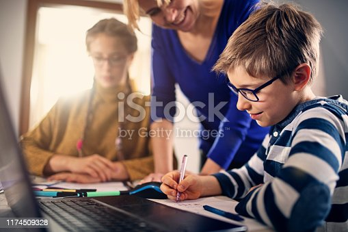 istock Mother helping kids to do homework 1174509328