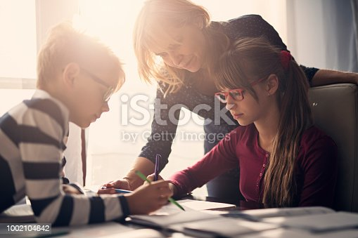 istock Mother helping kids with homework 1002104642