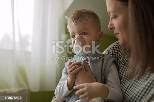 Mother helping little boy using nebulizer during inhalation therapy