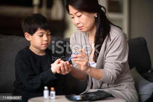 A mother and son are sitting together in a living room. She is helping him check his blood sugar levels because he is diabetic.