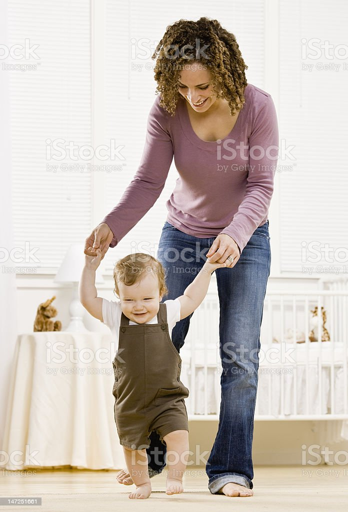 Mother helping son learn to walk royalty-free stock photo