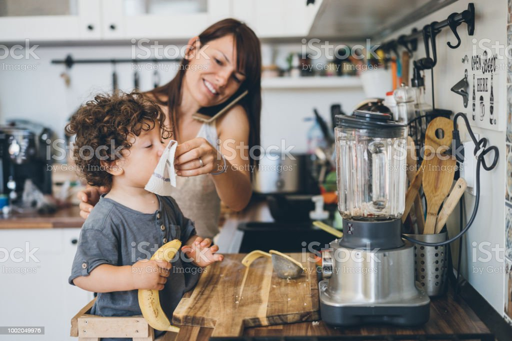 Mother helping son to blow his nose stock photo