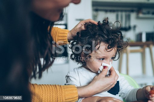 Mother helping son to blow his nose at home