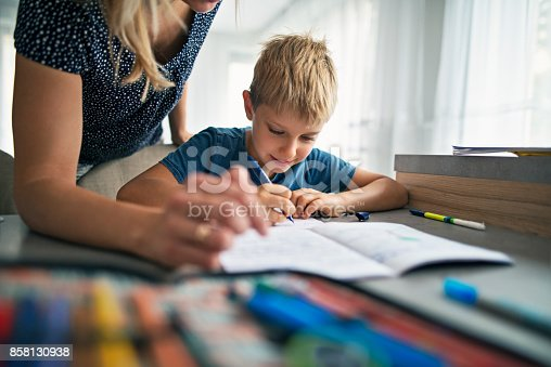 858130938 istock photo Mother helping son to do his homework 858130938