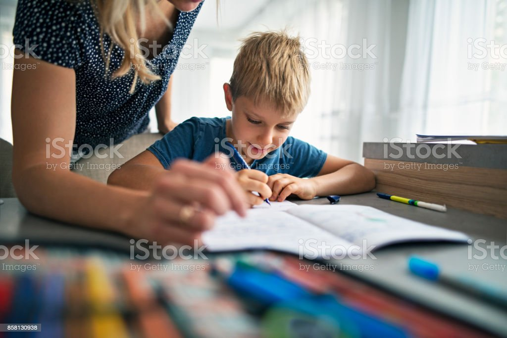 Mother helping son to do his homework stock photo