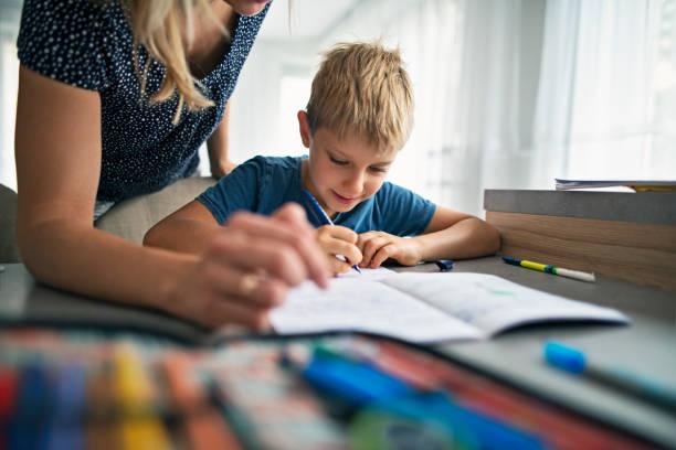 hijo de madre ayudando a hacer su tarea - clase de escritura fotografías e imágenes de stock