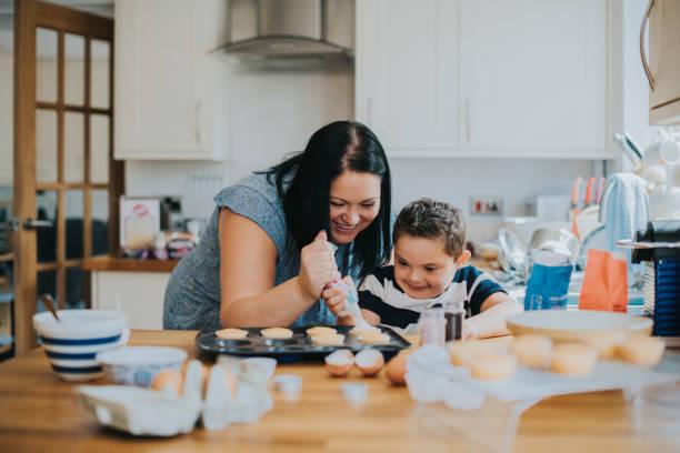 カップケーキにフロスティングを配置する母を助ける息子 - disabilitycollection ストックフォトと画像