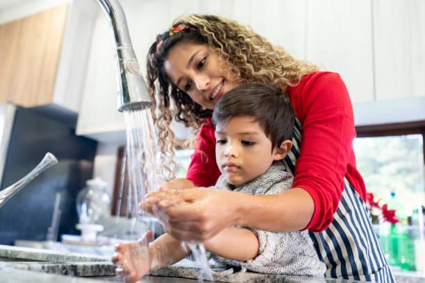mutter hilft sohn waschen seine hand nach der herstellung von keksen - wasch oder spülbecken stock-fotos und bilder