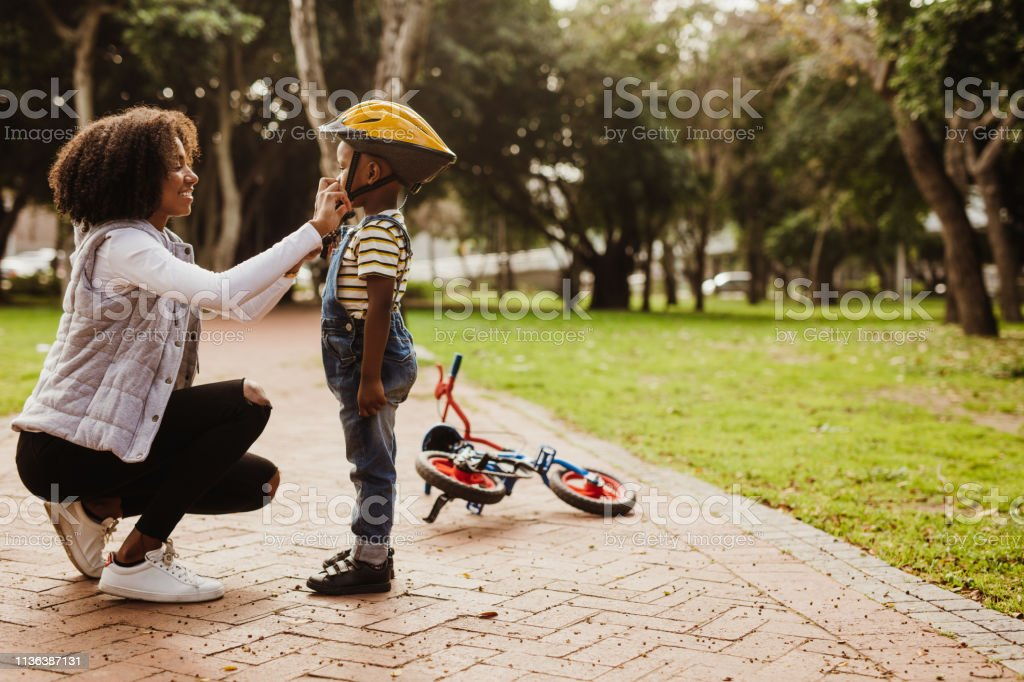 Mother helping son wearing helmet for cycling stock photo
