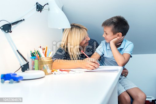858130938 istock photo Mother helping son with homework 1042264576