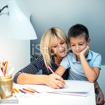 istock Mother helping son with homework 1042569430