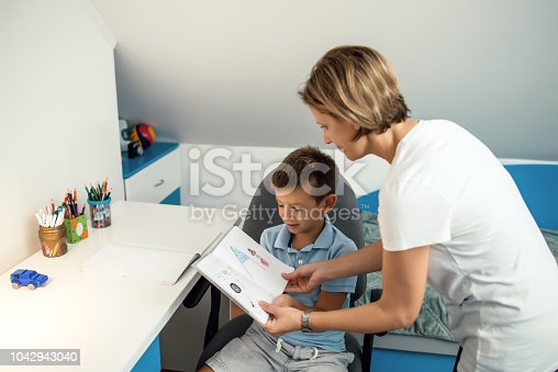 istock Mother helping son with homework 1042943040