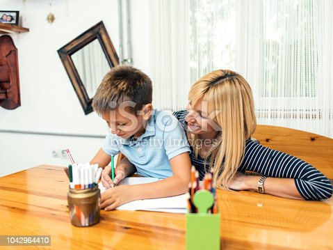 istock Mother helping son with homework 1042964410