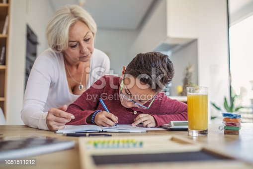 680535874 istock photo Mother helping son with homework 1051511212