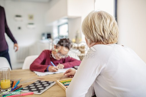 680535874 istock photo Mother helping son with homework 1055299332