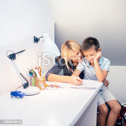 istock Mother helping son with homework 1065846618