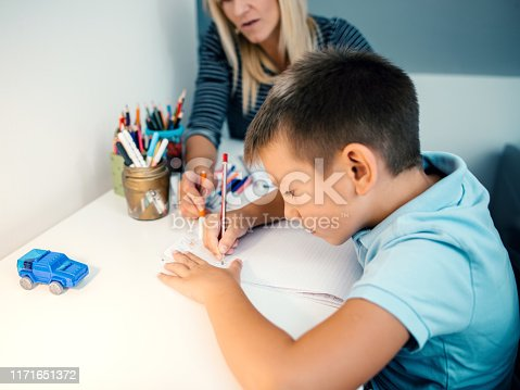 858130938 istock photo Mother helping son with homework 1171651372