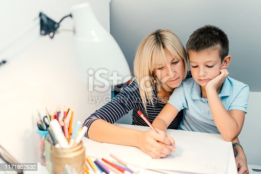 858130938 istock photo Mother helping son with homework 1171652632