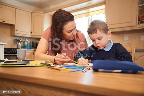 858130938 istock photo Mother helping son with homework 1211212139