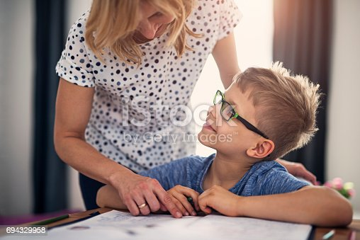 680535874 istock photo Mother helping son with homework 694329958