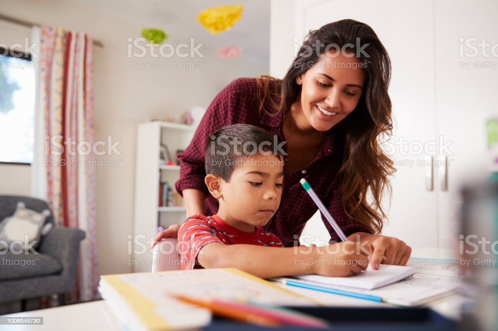 Mother Helping Son With Homework Sitting At Desk In Bedroom stock photo