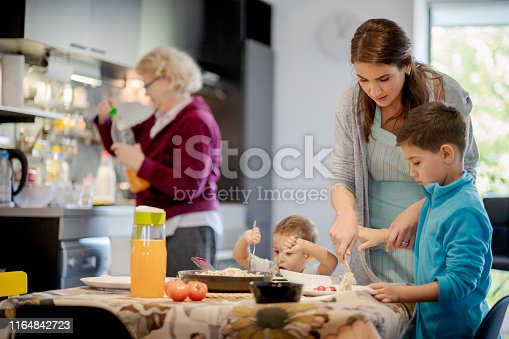 Mother helping older son serving food, toddler trying to eat on his own