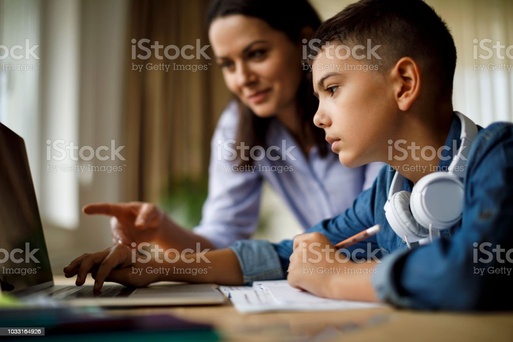 Mother helping teenager with homework stock photo