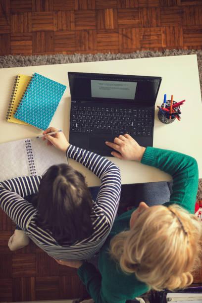 Mutter hilft ihren Töchtern, Schulhausaufgaben zu Hause während COVID-19 Pandemie zu beenden – Foto