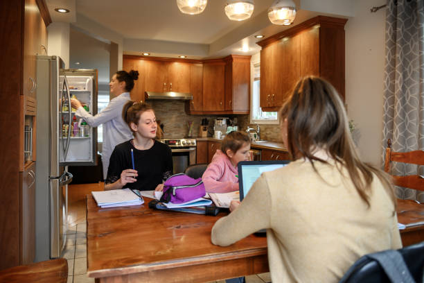 mother helping to her daughters to finish school homework during coronavirus quarantine - covid stock pictures, royalty-free photos & images