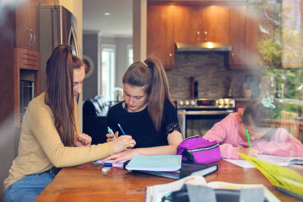 mother helping to her daughters to finish school homework during coronavirus quarantine - quarantined family stock pictures, royalty-free photos & images