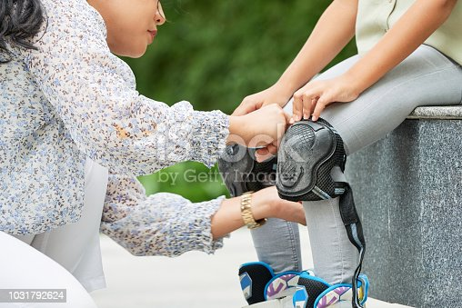 Mother helping daughter with wearing knee pads for roller skating