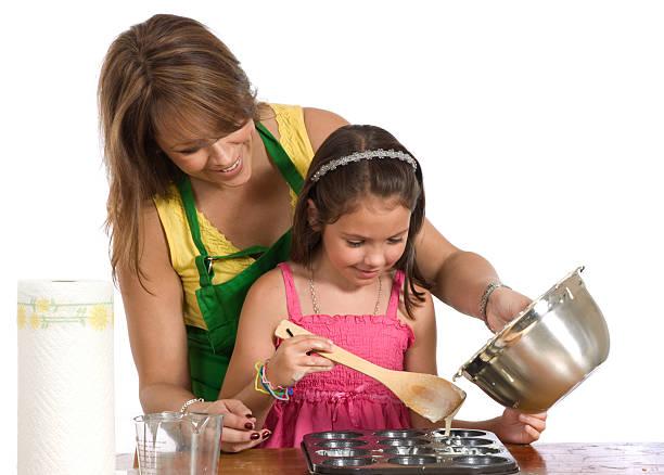 Mother Helps Daughter Fill Muffin Pan stok fotoğrafı