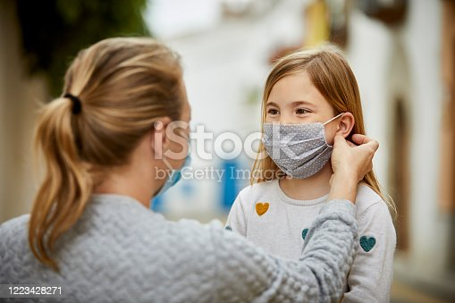 A mother wearing surgical mask helps daughter putting home made face mask during coronavirus pandemic.