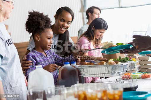 istock Mother helps daughter serve food in soup kitchen 641609322