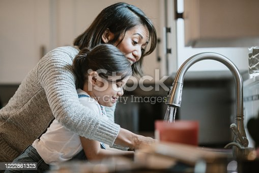 A mom teaches her little girl how to properly wash and disinfect her hands to keep them free of virus and bacteria germs.  Part of a regular routine, or the new normal with social distancing and working from home during the Covid-19 Pandemic.