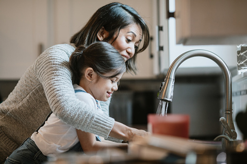 Mother Helps Daughter Wash Hands With Good Technique