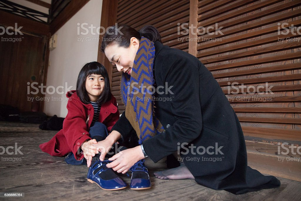 Mother helps doing up her daughter's shoelaces stock photo