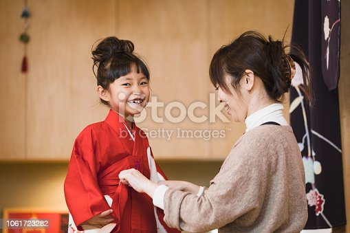 Japanese mother helping her daughter wearing Kimono to celebrate New Year.