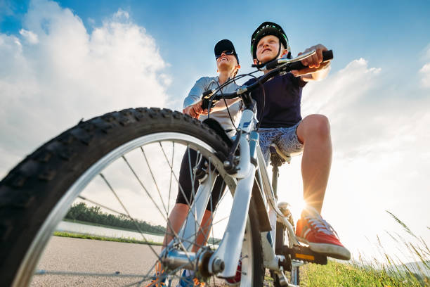 Mother helps her little son start to ride a bicycle stock photo
