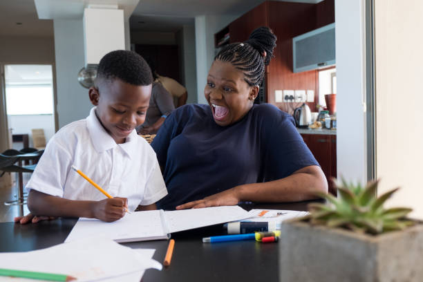 Mother helps her son with his homework stock photo
