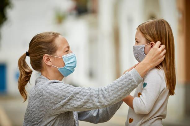Mutter hilft kleine Tochter auf Schutz Gesichtsmaske für COVID-19 setzen – Foto