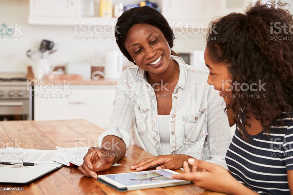 Mother Helps Teenage Daughter With Homework Using Digital Tablet stock photo