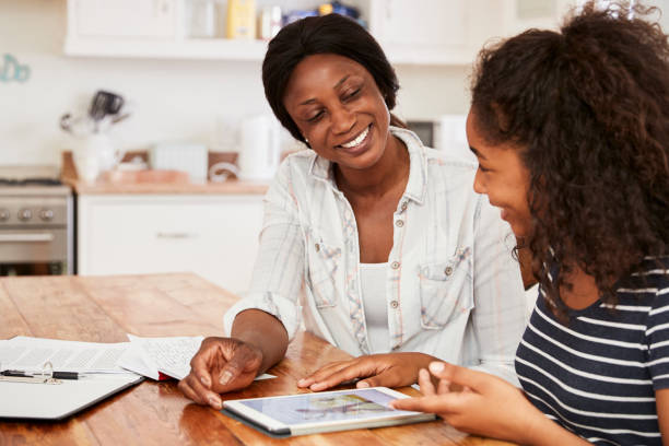 mother helps teenage daughter with homework using digital tablet - teenager stock photos and pictures