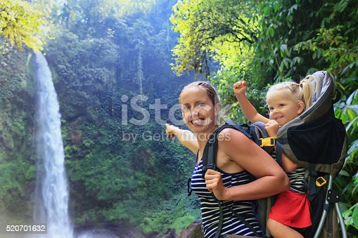 istock Mother hold baby girl in backpack on waterfall background 520701632